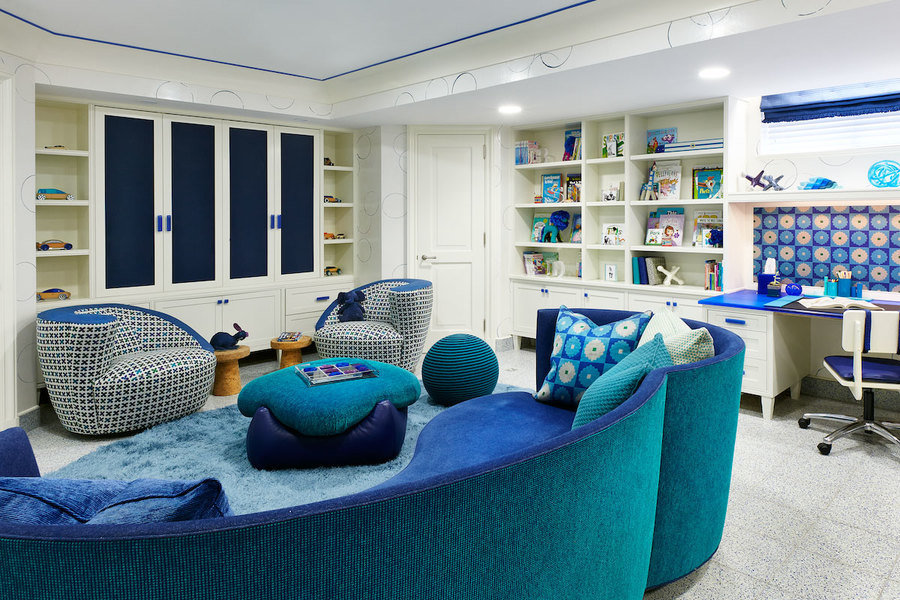 Mixed patterns and vibrant blue rug and furniture give this playroom designed by Jenny Kirschner a pl