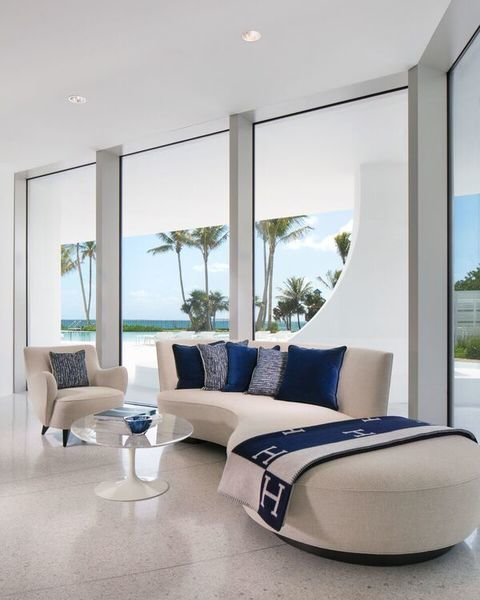 Punctuated by navy throw pillows and a blanket, this room designed by Pierre-Yves Rochon creates inte