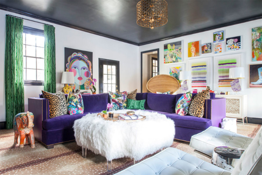 An ultra violet couch and punches of purple reflected in artwork on the walls and throw pillows on th