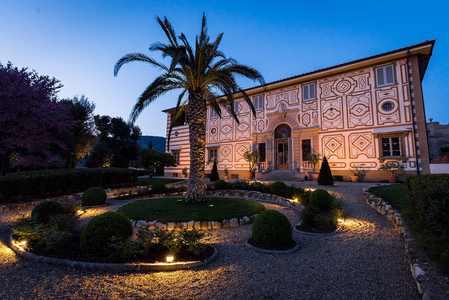 An exterior view of Villa Capponi shows its symmetrical graffito patterns adorn its cream plaster ele