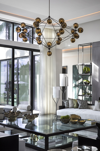 A contemporary cluster of illuminated orbs becomes the dramatic focal point of a living room designed